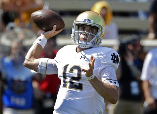 (AP Photo/Chuck Burton). Notre Dame's Ian Book (12) looks to pass against Wake Forest in the first half of an NCAA college football game in Winston-Salem, N.C., Saturday, Sept. 22, 2018.