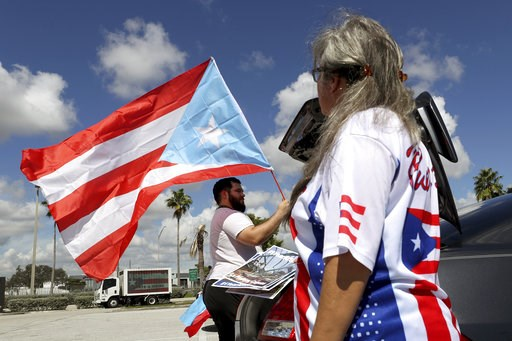 (Mike Stocker /South Florida Sun-Sentinel via AP). Aaron and Diana Umpirerre gather in the parking lot to meet others to head to West Palm Beach for a protest, Saturday, Sept. 22, 2018 in Hollywood, Fla.  Activists marking the one-year anniversary of H...