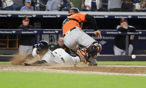 (AP Photo/Frank Franklin II). New York Yankees' Didi Gregorius slides past Baltimore Orioles catcher Caleb Joseph to score during the eleventh inning of a baseball game Saturday, Sept. 22, 2018, in New York. The Yankees won 3-2.