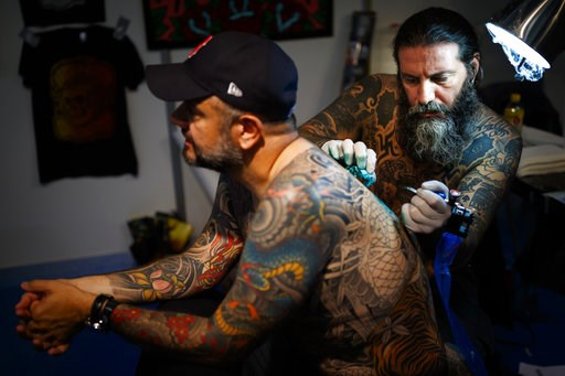 (Valentin Flauraud/Keystone via AP). A tattoo artist tattooes a visitor at the fourth edition of the Montreux Tattoo Convention in Montreux, Switzerland, Saturday, Sept. 22, 2018. Over 150 tattoo artists from 22 couttries gather for 3 days in Montreux.