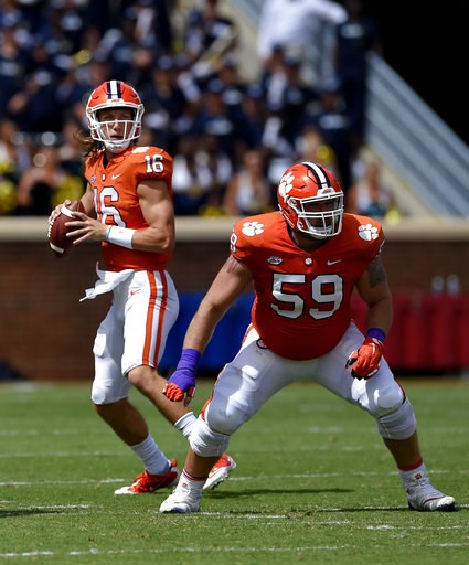 (AP Photo/Richard Shiro, File). FILE - In this Saturday, Sept. 15, 2018, file photo, Clemson quarterback Trevor Lawrence drops back to pass with blocking help from Gage Cervenka (59) during the first half of an NCAA college football game against Georgi...