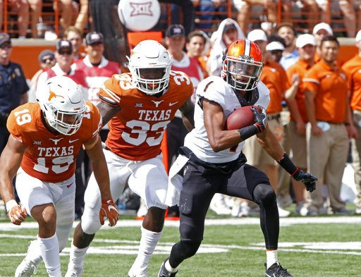 (AP Photo/Michael Thomas, File). FILE - In this Oct. 21, 2017, file photo, Oklahoma State receiver Jalen McCleskey (1) runs after a catch against Texas defenders Brandon Jones (15) and Gary Johnson (33) during the second half of an NCAA college footbal...