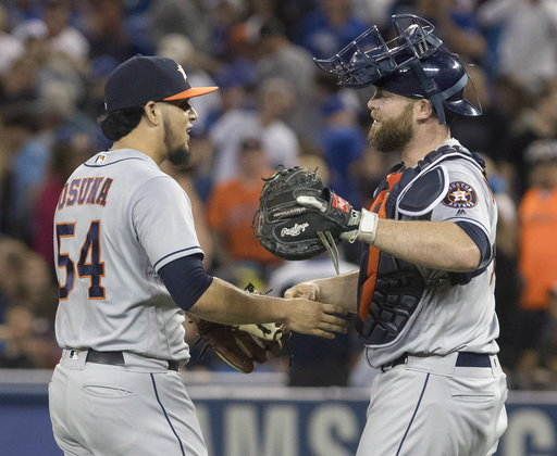 (Fred Thornhill/The Canadian Press via AP). Houston Astros pitcher Roberto Osuna celebrates with catcher Brian McCann after they defeated the Toronto Blue Jays in a baseball game in Toronto on Monday Sept. 24, 2018.