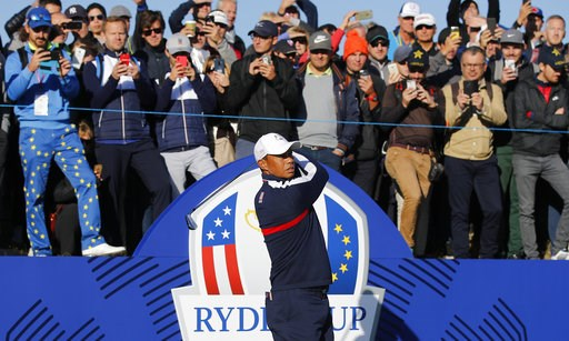 (AP Photo/Francois Mori). Spectators watch above as Tiger Woods of the US plays from the 1st tee during practice at Le Golf National in Guyancourt, outside Paris, France, Tuesday, Sept. 25, 2018. The 42nd Ryder Cup will be held in France from Sept. 28-...