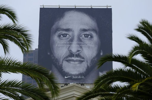 (AP Photo/Eric Risberg, File). FILE- In this Sept. 5, 2018, file photo palm trees frame a large billboard on top of a Nike store that shows former San Francisco 49ers quarterback Colin Kaepernick at Union Square in San Francisco. Nike Inc. reports earn...