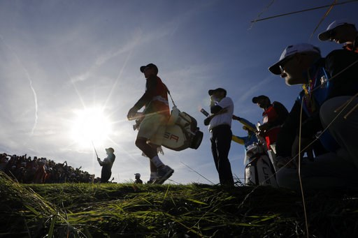 (AP Photo/Laurent Cipriani). Webb Simpson of the US is silhouetted as he tees off on the 13th hole during his foursome match on the second day of the 2018 Ryder Cup at Le Golf National in Saint Quentin-en-Yvelines, outside Paris, France, Saturday, Sept...