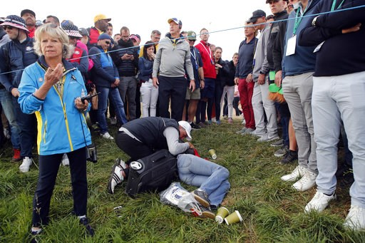 (AP Photo/Francois Mori, File). FILE - In this Friday, Sept. 28, 2018 file photo a man tends an unidentified injured woman after she was hit by US player Brooks Koepka's ball on the 6th hole during a fourball match on the opening day of the 42nd Ryder ...