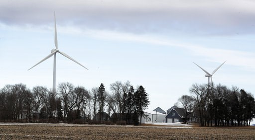 (AP Photo/Charlie Neibergall, File). FILE - In this Feb. 2, 2018 file photo, wind turbines stand over a farmhouse  near Northwood, Iowa. A new study out of Harvard finds that ramping up wind power in America would also dial up the nation's temperatures.