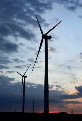 (AP Photo/Charlie Riedel, File). FILE - In this June 1, 2017 file photo, wind turbines, which are part of the Lost Creek Wind Farm, stand against the sky at dusk near King City, Mo.  A new study out of Harvard finds that ramping up wind power in Americ...