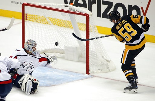 (AP Photo/Gene J. Puskar). Pittsburgh Penguins' Jake Guentzel (59) gets the put behind Washington Capitals goaltender Braden Holtby for a goal during the first period of an NHL hockey game in Pittsburgh, Thursday, Oct. 4, 2018.