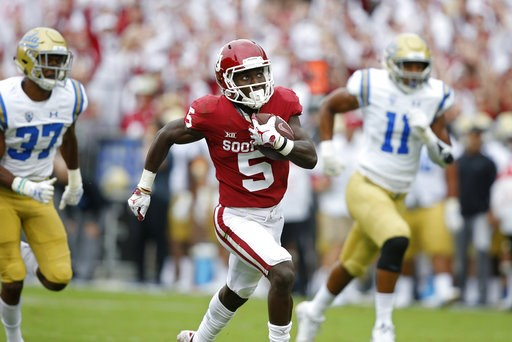 (AP Photo/Sue Ogrocki, File). FILE - In this Sept. 8, 2018, file photo, Oklahoma wide receiver Marquise Brown (5) runs away from UCLA defensive back Quentin Lake (37) and linebacker Keisean Lucier-South (11) for a touchdown in the first quarter of an N...
