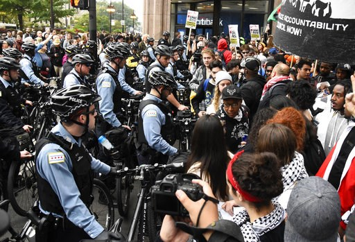 (AP Photo/Matt Marton). Protesters stand near police in the downtown area after a jury convicted white Chicago police officer Jason Van Dyke of second-degree murder in the 2014 shooting of black teenager Laquan McDonald Friday, Oct. 5, 2018, in Chicago...