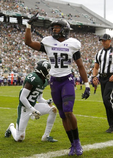 (AP Photo/Al Goldis). Northwestern's JJ Jefferson (12) celebrates his touchdown reception against Michigan State's Tre Person (24) during the second quarter of an NCAA college football game, Saturday, Oct. 6, 2018, in East Lansing, Mich.