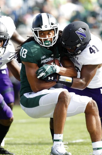 (AP Photo/Al Goldis). Michigan State's Felton Davis (18) is stopped by Northwestern's Jared McGee (41) during the first quarter of an NCAA college football game, Saturday, Oct. 6, 2018, in East Lansing, Mich.