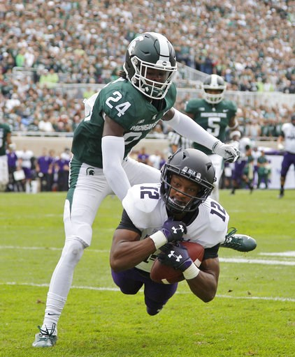 (AP Photo/Al Goldis). Northwestern's JJ Jefferson (12) catches a pass for a touchdown against Michigan State's Tre Person (24) during the second quarter of an NCAA college football game, Saturday, Oct. 6, 2018, in East Lansing, Mich.