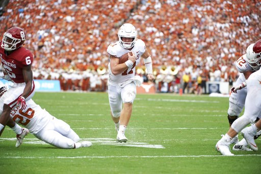 (AP Photo/Cooper Neill). Texas quarterback Sam Ehlinger (11) scrambles for a 9-yard touchdown against Oklahoma during the first half of an NCAA college football game at the Cotton Bowl, Saturday, Oct. 6, 2018, in Dallas.