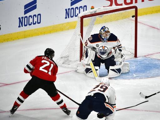 (Bjorn Larsson Rosvall /TT News Agency via AP). New Jersey Devils' Kyle Palmieri, left, scores, during the season-opening NHL Global Series hockey match between Edmonton Oilers and New Jersey Devils at Scandinavium in Gothenburg, Sweden, Saturday, Oct....