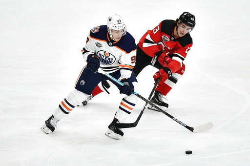 (Bjorn Larsson Rosvall /TT News Agency via AP). Edmonton Oilers' Ryan Nugent-Hopkins and New Jersey Devils' Nico Hischier vie for the puck, during the season-opening NHL Global Series hockey match between Edmonton Oilers and New Jersey Devils at Scandi...