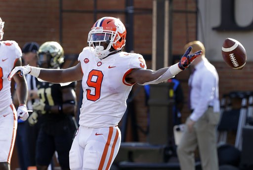 (AP Photo/Chuck Burton). Clemson's Travis Etienne (9) celebrates his touchdown run against Wake Forest during the first half of an NCAA college football game in Charlotte, N.C., Saturday, Oct. 6, 2018.