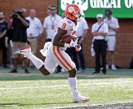 (AP Photo/Chuck Burton). Clemson's Travis Etienne (9) runs for a touchdown against Wake Forest during the first half of an NCAA college football game in Charlotte, N.C., Saturday, Oct. 6, 2018.