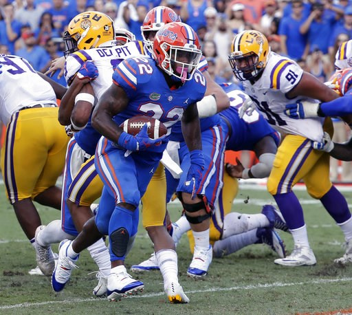 (AP Photo/John Raoux). Florida running back Lamical Perine (22) runs past the LSU defense for a 1-yard touchdown during the first half of an NCAA college football game, Saturday, Oct. 6, 2018, in Gainesville, Fla.