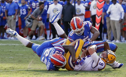 (AP Photo/John Raoux). LSU quarterback Joe Burrow (9) is tackled by Florida defensive back Chauncey Gardner-Johnson (23) and defensive back CJ Henderson, right, after running for a first down during the first half of an NCAA college football game, Satu...