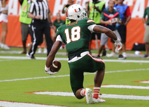 (AP Photo/Lynne Sladky). Miami wide receiver Lawrence Cager (18) scores a touchdown during the first half of an NCAA college football game against Florida State, Saturday, Oct. 6, 2018, in Miami Gardens, Fla.