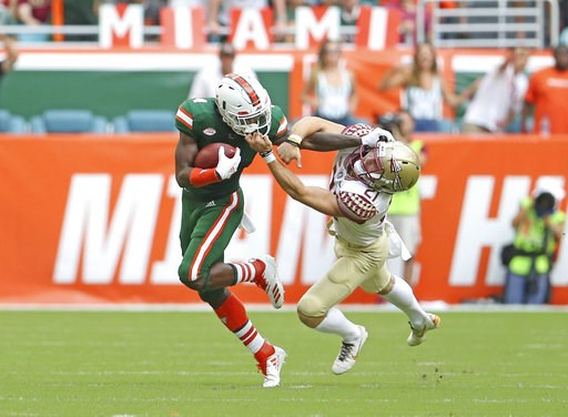 (David Santiago/Miami Herald via AP). Florida State punter Logan Tyler, right, grabs Miami wide receiver Jeff Thomas by the mask during the first half of an NCAA college football game, Saturday, Oct. 6, 2018, in Miami Gardens, Fla.
