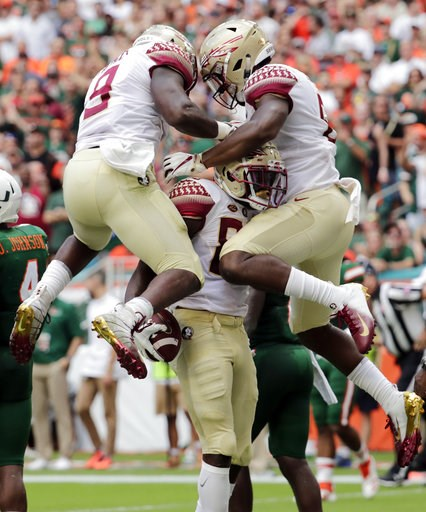 (AP Photo/Lynne Sladky). Florida State wide receiver Keith Gavin, center, celebrates with running back Jacques Patrick (9) and tight end Tre' McKitty, right, after scoring a touchdown during the first half of an NCAA college football game against Miami...