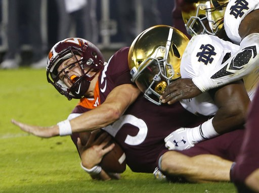 (AP Photo/Steve Helber). Virginia Tech quarterback Ryan Willis (5) is slammed to the ground on third down near the goal line during the first half of an NCAA college football game in Blacksburg, Va., Saturday, Oct. 6, 2018.