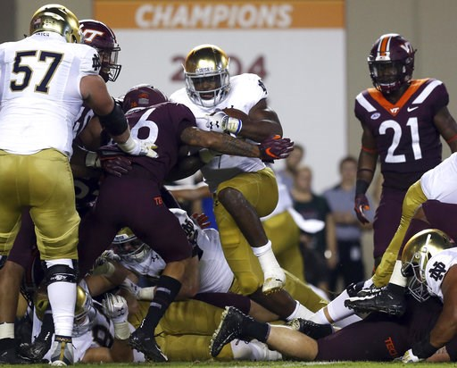 (Matt Gentry/The Roanoke Times via AP). Notre Dame's Dexter Williams (2) fights his way into the end zone for a touchdown against Virginia Tech during the first half of an NCAA college football game Saturday, Oct. 6, 2018, in Blacksburg, Va.