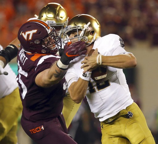 (Matt Gentry/The Roanoke Times via AP). Virginia Tech's Jarrod Hewitt (55) grabs Notre Dame quarterback Ian Book (12) by the face mask and is called for a personal foul during the first quarter of an NCAA college football game Saturday, Oct. 6, 2018, i...