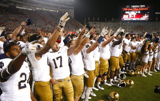 (AP Photo/Steve Helber). Notre Dame players celebrate a 45-23 win over Virginia Tech in an NCAA college football game in Blacksburg, Va., Saturday, Oct. 6, 2018.