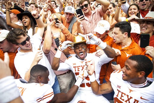 (Nick Wagner/Austin American-Statesman via AP). Texas defensive back Josh Thompson (29) celebrates with fans while wearing the Golden Hat following Texas' 48-45 win over Oklahoma in an NCAA college football game at the Cotton Bowl, Saturday, Oct. 6, 20...