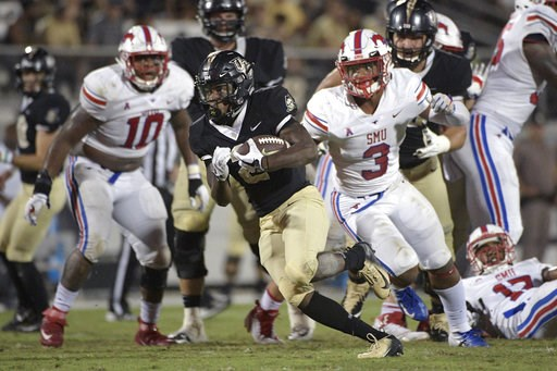 (AP Photo/Phelan M. Ebenhack). Central Florida running back Otis Anderson, center, breaks free for a 30-yard rushing touchdown past SMU defensive tackle Demerick Gary (10) and linebacker Delano Robinson (3) during the second half of an NCAA college foo...