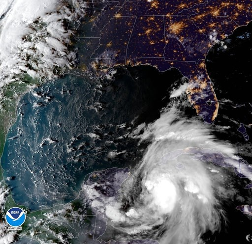 (NOAA via AP). This satellite image provided by the National Oceanic and Atmospheric Administration shows a view of Tropical Storm Michael, lower right, churning as it heads toward the Florida Panhandle, Sunday, Oct. 7, 2018, at 6:52 p.m. Eastern Time.