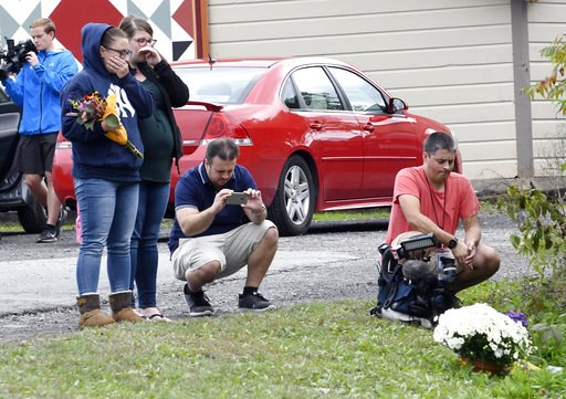 (AP Photo/Hans Pennink). People place flowers, Sunday, Oct. 7, 2018, at the scene where 20 people died as the result of a limousine crashing into a parked and unoccupied SUV at an intersection a day earlier, in Schoharie, N.Y.
