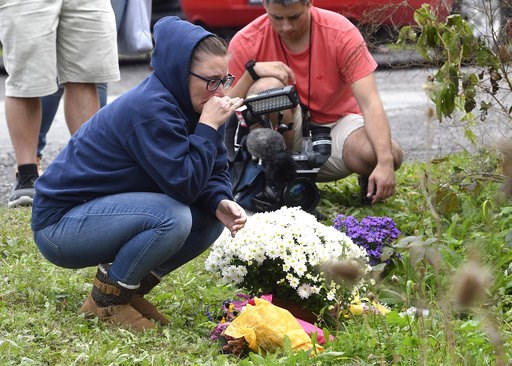 (AP Photo/Hans Pennink). A woman kneels after placing flowers, Sunday, Oct. 7, 2018, at the scene where 20 people died as the result of a limousine crashing into a parked and unoccupied SUV at an intersection a day earlier, in Schoharie, N.Y.