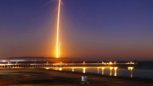 (of San Luis Obispo) via AP). Two streaks in this long exposure photo show a SpaceX Falcon 9 rocket lifting off, left, from Vandenberg Air Force Base, as seen from Pismo Beach, Calif. Sunday, Oct. 7, 2018, and then its first stage returning, right, to ...