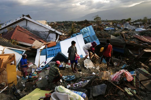 (AP Photo/Dita Alangkara). In this Friday, Oct. 5, 2018, photo, a family scavenges for salvageable items from the ruins of their house at Petobo neighborhood which was wiped out by liquefaction caused by a massive earthquake in Palu, Central Sulawesi, ...