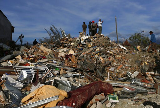 (AP Photo/Dita Alangkara). In this Sunday, Oct. 7, 2018, photo, people stand on top of rubble and dried mud as they survey the damage of the Petobo neighborhood which was wiped out by earthquake-triggered liquefaction in Palu, Central Sulawesi, Indones...