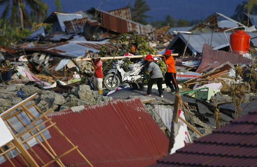 (AP Photo/Dita Alangkara). In this Friday, Oct. 5, 2018, photo, men carry a salvaged motorbike from the Petobo neighborhood wiped out by liquefaction caused by a massive earthquake in Palu, Central Sulawesi, Indonesia. Many in the decimated village had...