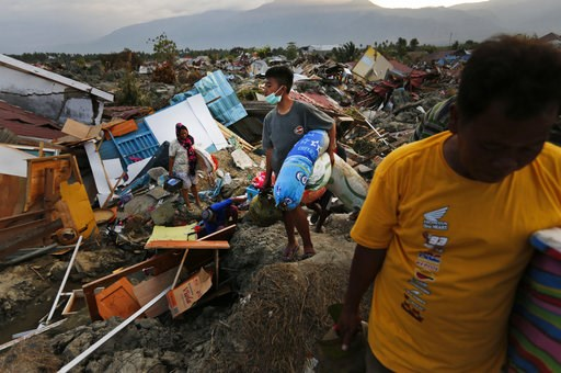 (AP Photo/Dita Alangkara). In this Friday, Oct. 5, 2018, photo, a family carries salvageable items they scavenged from the ruins of their house in the Petobo neighborhood which was wiped out by liquefaction caused by an earthquake in Palu, Central Sula...