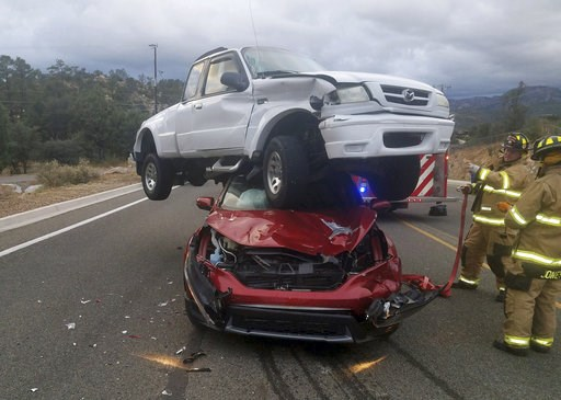 (Ralph Lucas/Prescott Fire Department via AP). In this Sunday, Oct. 7, 2018 photo provided by the Prescott Fire Department, firefighters work the scene of an accident in Prescott, Ariz. Firefighters in Prescott said nobody was hurt after a pickup truck...