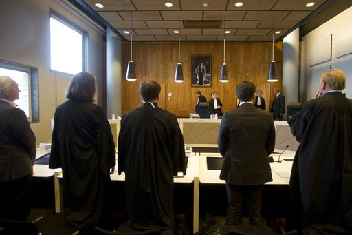 (AP Photo/Peter Dejong). Lawyers representing Urgenda, left, and the Dutch Government, right, rise as presiding judge Marie-Anne Tan-de Sonnaville, rear center right, enters the appeals court in The Hague, Netherlands, Tuesday, Oct. 9, 2018, where the ...