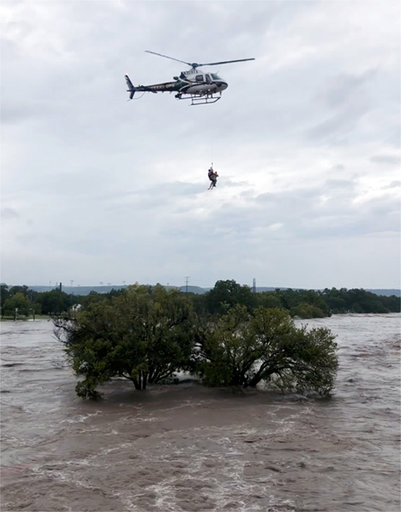(Texas Parks and Wildlife Department via AP). This photo from video provided by the Texas Parks and Wildlife Department shows a helicopter crew from the Texas Department of Public Safety performing a rescue from the South Llano River near Junction, Tex...