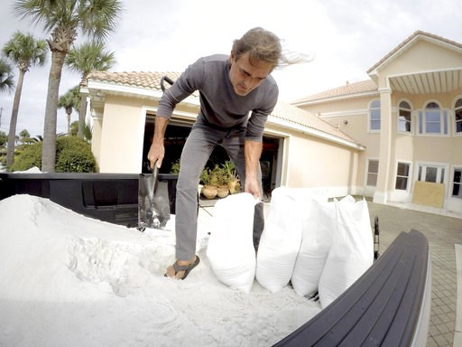 (Nick Tomecek/Northwest Florida Daily News via AP). Rick Johnson fills sand bags on Tuesday, Oct. 9, 2018 at his Okaloosa Island home in Fort Walton Beach, Fla.,  in preparation for Hurricane Michael.