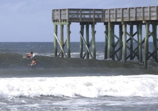(Patti Blake/News Herald via AP). Surfers paddle past the St.Andrews State Park Pier Tuesday, Oct.9, 2018,  at Panama City Beach, Fla.