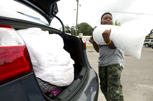 (Joshua Boucher/News Herald via AP). Xavier McKenzie puts a twenty pound bag of ice into his family's car in Panama City, Fla., as Hurricane Michael approaches on Tuesday, Oct.9, 2018. He and his family do not live in a storm surge area, and instead pr...