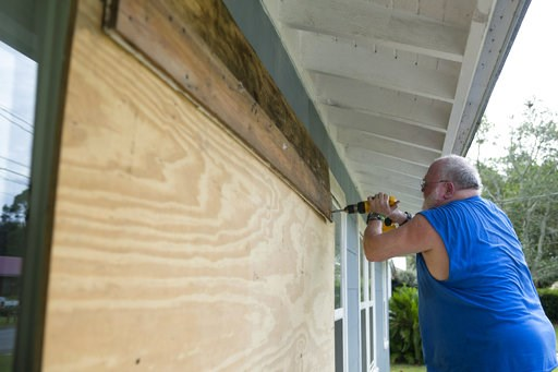 (Joshua Boucher/News Herald via AP). David Hayes boards up a window at this home in Panama City, Fla., as Hurricane Michael approaches on Tuesday, Oct. 9, 2018.